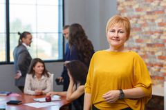 A female office worker is standing in a yellow sweater. In the background, the rings are discussed. An adult female office worker in a yellow sweater stands in Royalty Free Stock Images