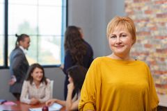 A female office worker stands in the foreground and smiles. In the background. Inside the office. An office worker is a blond women with short hair and in a Stock Image