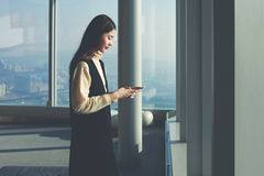 Female office worker of successful company is using mobile device Royalty Free Stock Images