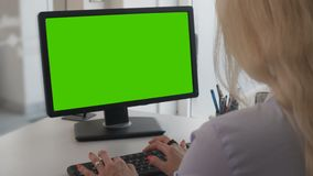 Female office worker typing documents on personal computer with green screen. Stock footage stock footage