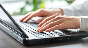 Female office worker. Female office worker typing on the keyboard Royalty Free Stock Photography