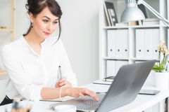 Female office worker using laptop at her workplace, browsing information, surfing the internet, side view portrait. Female office worker using laptop at her Royalty Free Stock Image