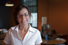 Female Office Worker Wearing Glasses and Smiling. A female office worker wearing eye glasses is standing in an office environment. Horizontal shot Stock Photos