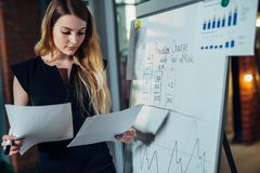 Female office worker working on her presentation standing near white board reading the report printed on paper Royalty Free Stock Images