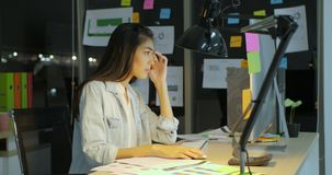 Female Office Worker Works Late Hours. She`s Alone on the Office. Her Table is Lit by a Lamp. Beautiful Asian Female Office Worker Works Late Hours. She`s Alone stock footage