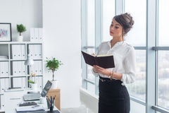 Female office worker writing down notes and day plan in her notebook, standing at workplace, front view portrait. Female office worker writing down notes and stock photos