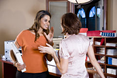 Female office workers chatting in copy room Royalty Free Stock Image
