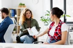 Female office workers giving each other papers Stock Photo