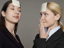 Female Office Workers With Sticky Notes On Foreheads Stock Image