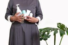 Woman hold cosmetics hands old person dispenser tube deodorant gel sponge vata white blue gray dress glasses one stock image
