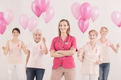 Female oncologist and cancer survivors. Medical concept, female oncologist and group of smiling breast cancer survivors with pink ribbons and balloons feeling royalty free stock images