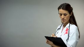 Female oncologist with pink ribbon writing diagnosis, deadly illness prevention. Stock photo royalty free stock photo
