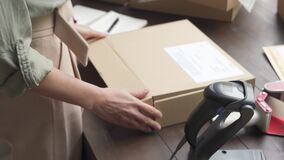 Female online store business owner packing ecommerce parcel shipping box.