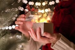 Female open Christmas gift box with gold ray of magic light on bokeh lights background Royalty Free Stock Photo