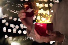 Female open red Christmas gift box with ray of magic light on bokeh lights background.  Royalty Free Stock Photography