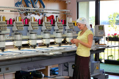 Female operator of automatic embroidery machines. Woman operator of automatic embroidery machines  working at her workplace Stock Photography
