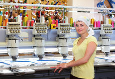Female operator of automatic embroidery machines. Woman operator of automatic embroidery machines working at her workplace stock images