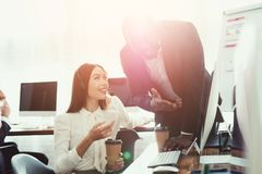 A female operator and a black guy are discussing something in their office. They work in the call center. They are in a good mood Stock Image