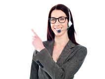 Female operator with headset pointing at something Stock Photos