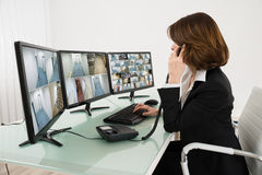 Female Operator Looking At Multiple Camera Footage On Computers. While Talking On Phone stock photography