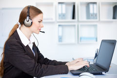 Female operator sitting at office desk with headse Royalty Free Stock Image