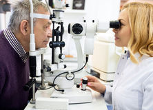 Female ophthalmic doctor check eyes  man in eye clinic. Female ophthalmic doctor check eyes to elderly men in eye clinic Royalty Free Stock Photo