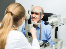 Female ophthalmologist and mature patient checking eyesight in c Stock Photo