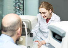 Female ophthalmologist and mature patient checking eyesight in c Stock Photos