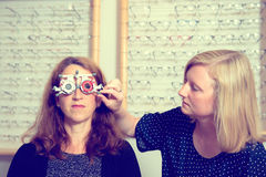 Female optican checking eyes of woman for new glasses Royalty Free Stock Photos