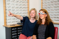 Female optican checking eyes of woman for new glasses Stock Photos