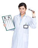 Female optician doctor hold eye chart and glasses Royalty Free Stock Photography
