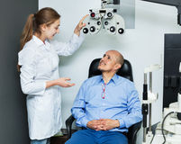 Female optician doing eye examination with  lamp Stock Photos