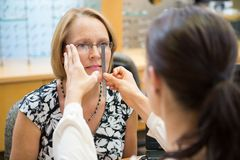 Female Optician Measuring Woman's Eyeglasses Stock Photo