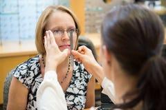 Female Optician Measuring Woman's Eyeglasses. Female optician measuring mature woman's eyeglasses in store stock photo
