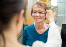 Female Optician Measuring Woman's Eyeglasses. Female optician measuring mature woman's eyeglasses in store stock photos