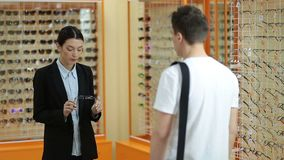 Female optician showing glasses to man at optics stock video footage