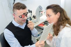 Female optician in surgery giving man eye test royalty free stock images