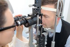 Female optician in surgery giving man eye test. Female optician in surgery giving men eye test female stock images