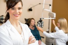 Female Optometrist With Colleague Examining. Portrait of female optometrist with colleague examining patient in background stock photography