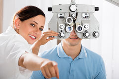Female Optometrist Doing Sight Testing For Patient stock image
