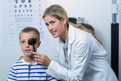 Female optometrist examining young patient with medical equipment Stock Photo