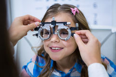 Female optometrist examining young patient with trial frame. In ophthalmology clinic Stock Photography