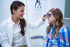 Female optometrist examining young patient with trial frame. In ophthalmology clinic royalty free stock image