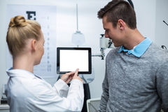 Female optometrist having discussion with patient on digital tablet Royalty Free Stock Photo