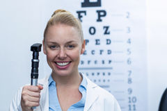 Female optometrist holding ophthalmoscope Royalty Free Stock Photography