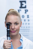 Female optometrist looking through ophthalmoscope Royalty Free Stock Photo