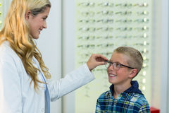 Female optometrist prescribing spectacles to young patient Stock Image