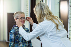 Female optometrist prescribing spectacles to young patient Stock Photography