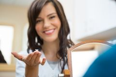 Female Optometrist Showing Contact Lens. Portrait of young female optometrist showing contact lens in optician store Stock Image