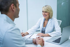 Female optometrist talking to male patient Royalty Free Stock Photos
